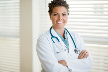 Confident Cancer Specialist Standing Arms Crossed In Clinic