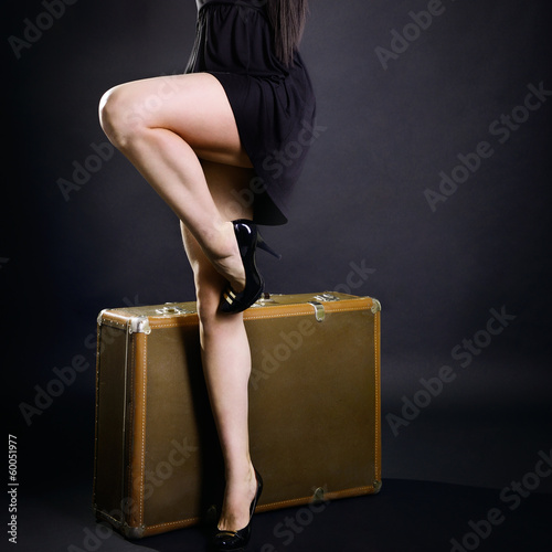 Travel sexy young woman hitchhiking with retro suitcase, vintage