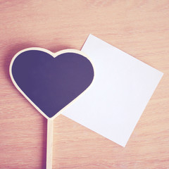 Heart shaped blackboard and note paper with copy space, retro fi