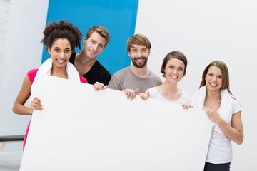 gruppe zeigt schild im fitnesscenter