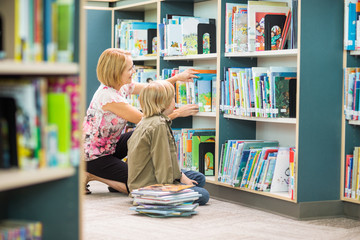 Teacher Assisting Boy In Selecting Books In Library