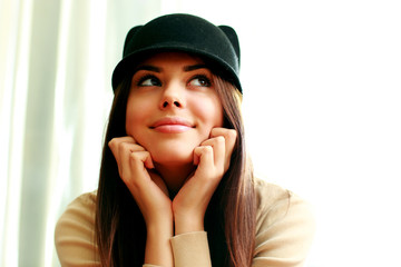 Young thoughtful happy woman in cute hat looking away