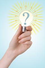 Question mark in lightbulb on light background