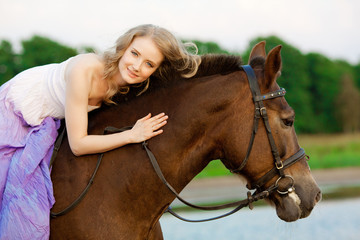 Beautiful woman riding a horse at sunset on the beach. Young gir