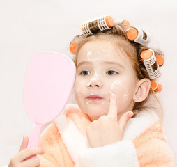 Cute little girl in hair curlers with mirror applying cream isol