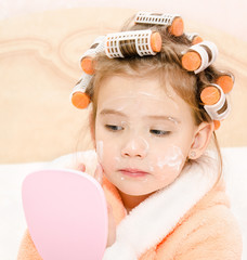 Cute little girl in hair curlers with mirror applying cream