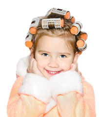 Portrait of smiling cute little girl in hair curlers and bathrob