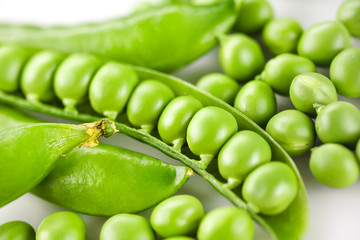 Pods of green peas on white background