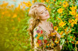 Young beautiful smiling woman in the blooming garden with flower