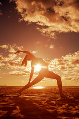Young beautiful slim woman silhouette practices yoga on the beac