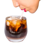 Female drinks cola with a straw over white background