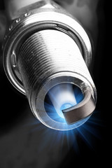 working spark plug with blue sparkle, isolated on black