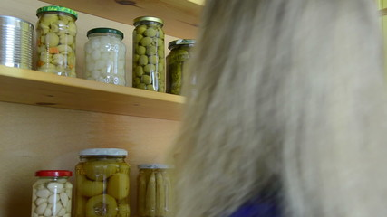 girl puts jars of canned cucumbers peppers in wooden cupboard