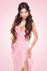 Beautiful brunette woman wearing in sexy luxury dress over pink