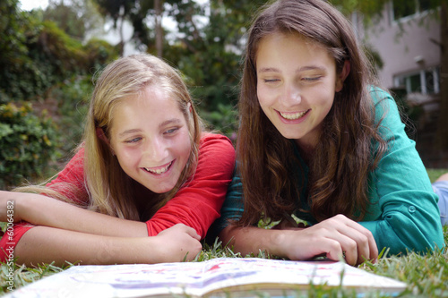 sisters read a book in the garden