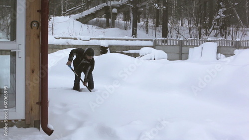 A man removes snow in front of house