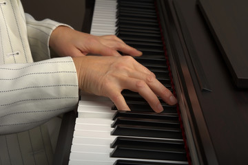 Two hands playing on the piano