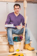 young contractor sitting on wooden ladder in home
