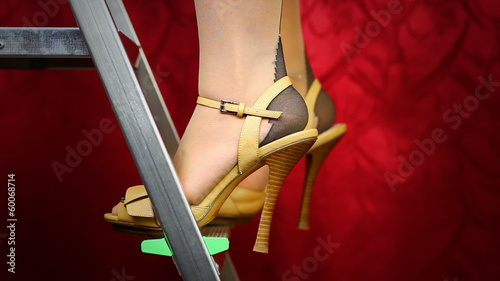 Women in high heels on step ladder