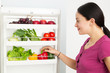 Young woman looking into a refrigerator