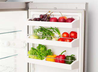 Open refrigerator full of fresh fruit and vegetables