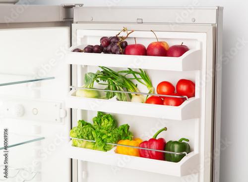 Open refrigerator full of fresh fruit and vegetables