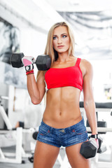 Beautiful fitness model with dumbbells