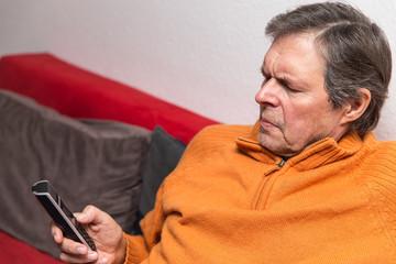 Senior im Wohnzimmer mit Mobiltelefon