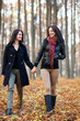 Two happy girlfriends walking in the woods while holding hands