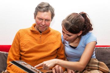 Tochter zeigt Vater ein Fotoalbum