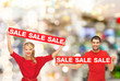 smiling woman and man with red sale signs