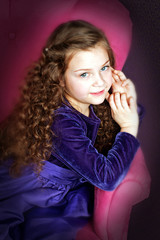 little girl with beautiful hair posing in chair