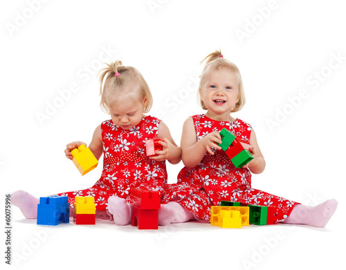 two twin girls in red dresses playing with blocks