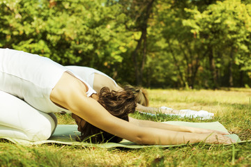 Two beautiful young women doing yoga class in nature.
