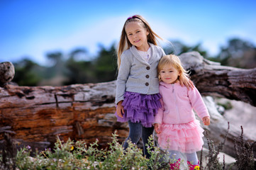 Two little girl wearing fashion clothes smile outdoor