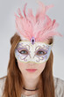 Beautiful teenage girl wearing carnival mask with pink feathers