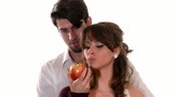 young lovers eating a red apple