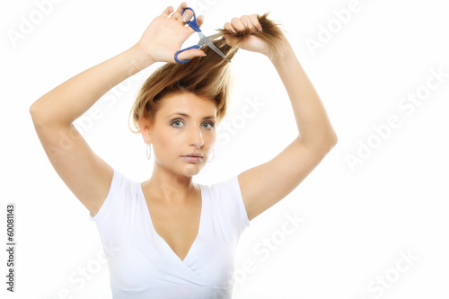 Unhappy woman cutting her hair with scissors isolated