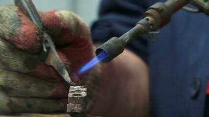 Repairman soldering parts of auto
