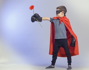 Superhero kid wearing boxing gloves and flower.