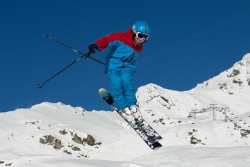 Skier in blue outfit doing a jump
