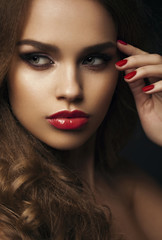 Portrait of beautiful girl with red lips, red manicure. Close up