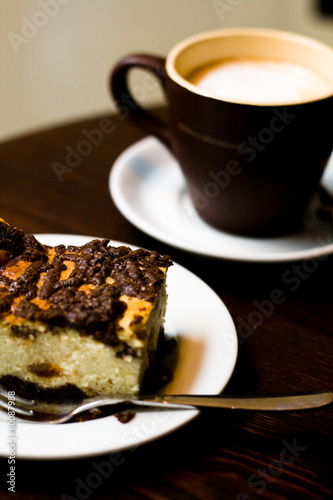 A cup of coffee in brown cup and cheese cake for breakfast
