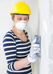 Female plasterer in hard hat polishing the wall.