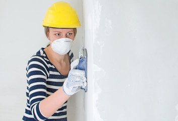 Female plasterer polishing the wall. Place for your text.
