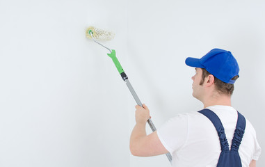 Painter in uniform paints the wall. Space for your text.