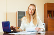 wistful blonde woman working with financial documents