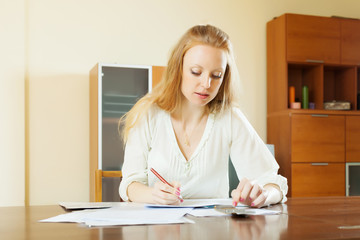 serious woman fills in financial documents