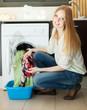 blonde woman using washing machine