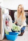 long-haired woman loading clothes into the washing machine